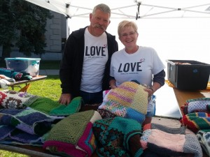 Joe and Christie wearing Love Squared shirts and holding a love squared blanket at tent city.