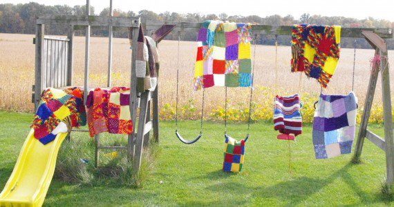 seven patchwork blanket hanging on a swing set