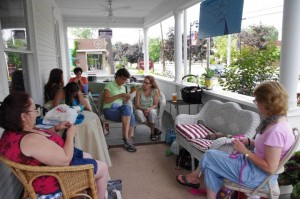 Women sitting and knitting on a large porch.