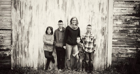 Leah and her four children standing against a barn door.